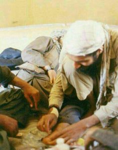 شیخ در حال بیرون آوردن خار از پای یک مسلمان